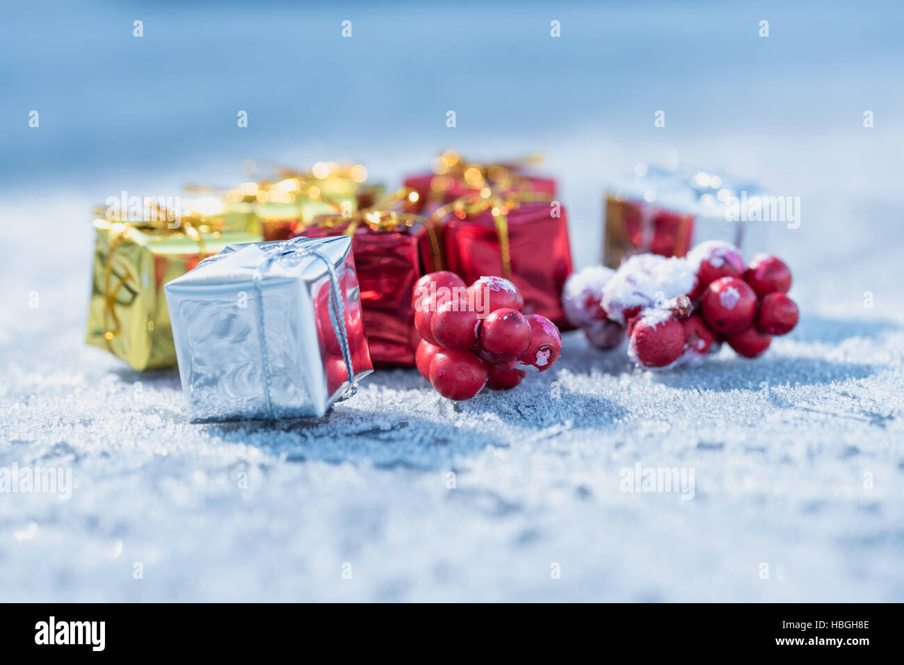 Little presents and red berries on frosty surface with light blue bokeh background - Stock Image