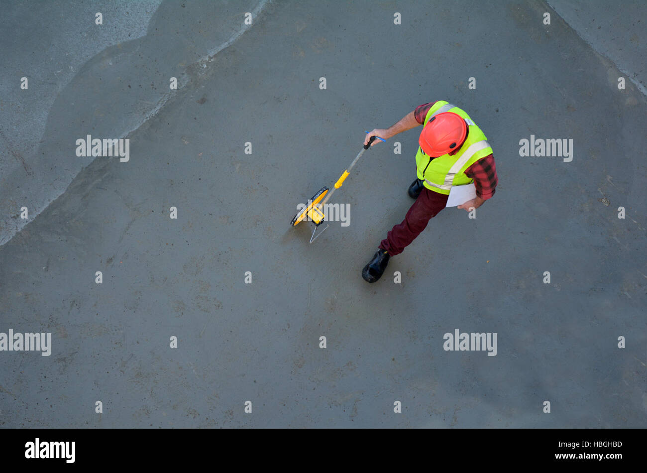Aerial view of a foreman builder measuring concrete floor with a rolling tape measure in a construction site. Copy - Stock Image