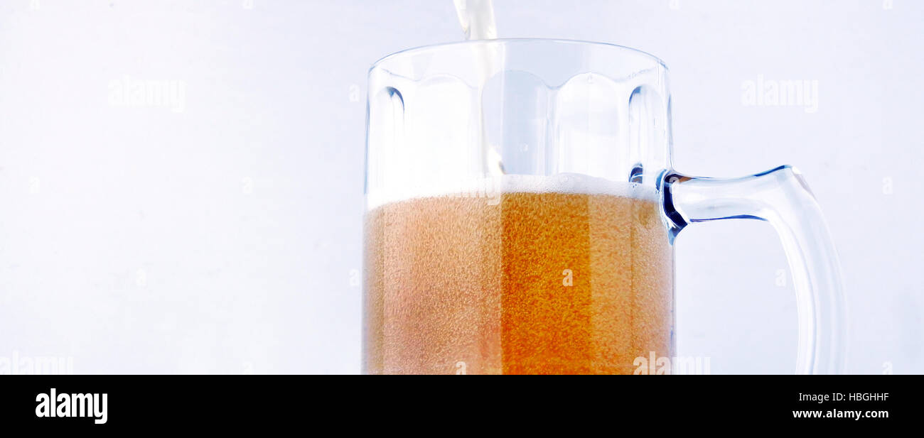 Low angle of pouring beer into a glass cup. Food and drinks background.Alcohol consumption concept. copy space - Stock Image