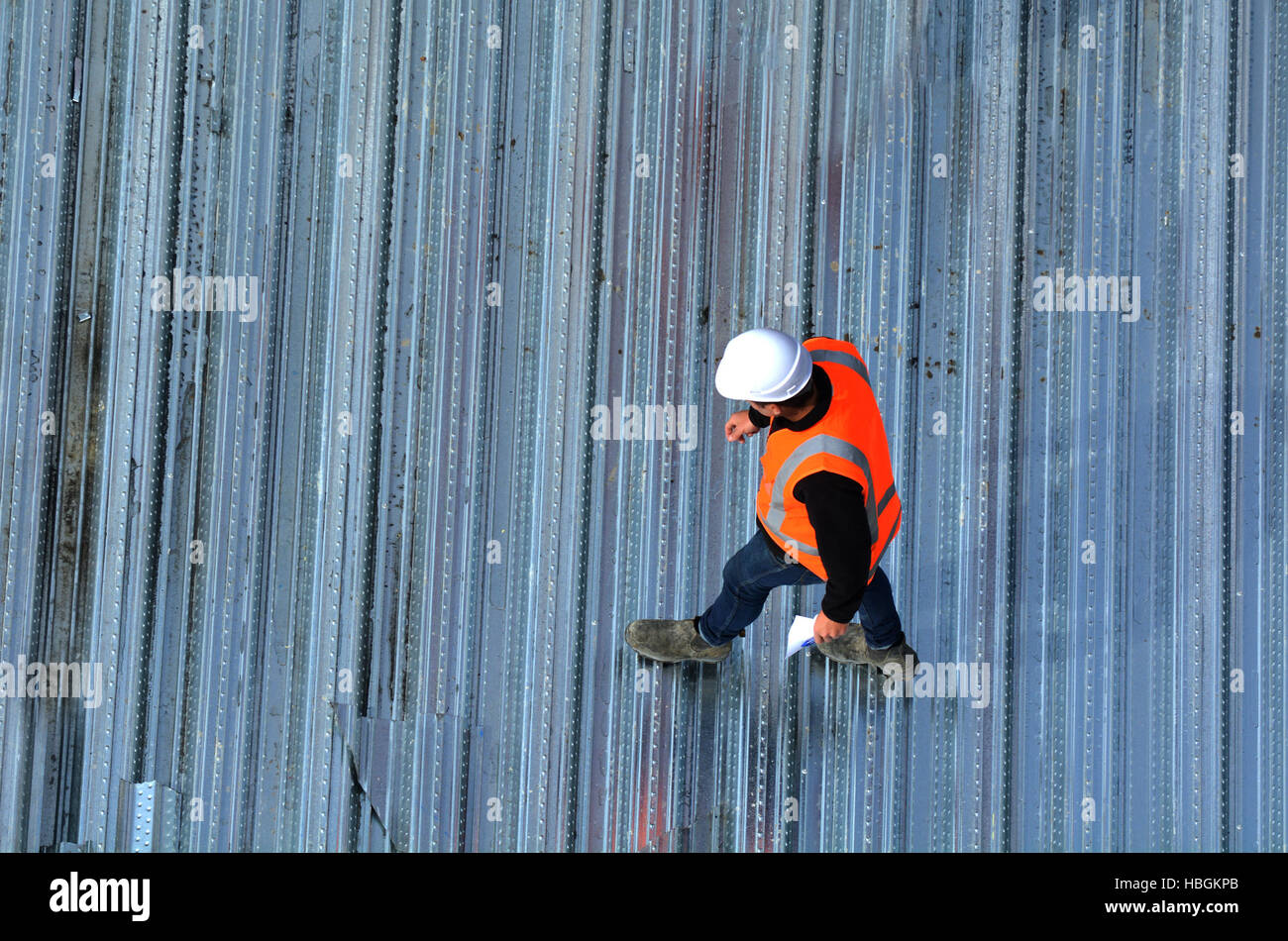 Aerial view of unrecognized civil engineers inspecting the work progress in a construction site. Building development - Stock Image