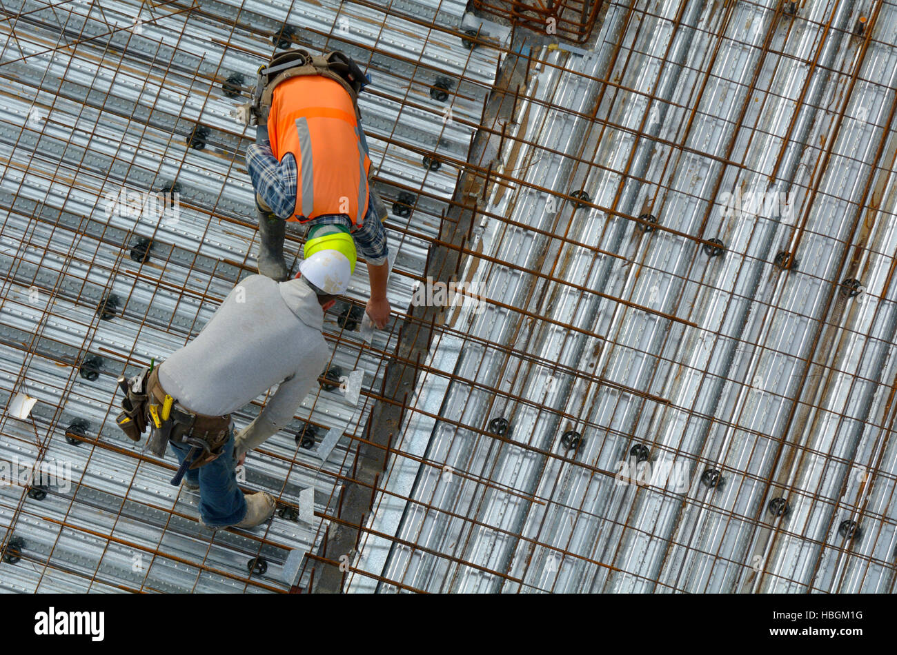 Aerial view of unrecognized civil engineer inspecting the work progress of a worker in a construction site. Building - Stock Image