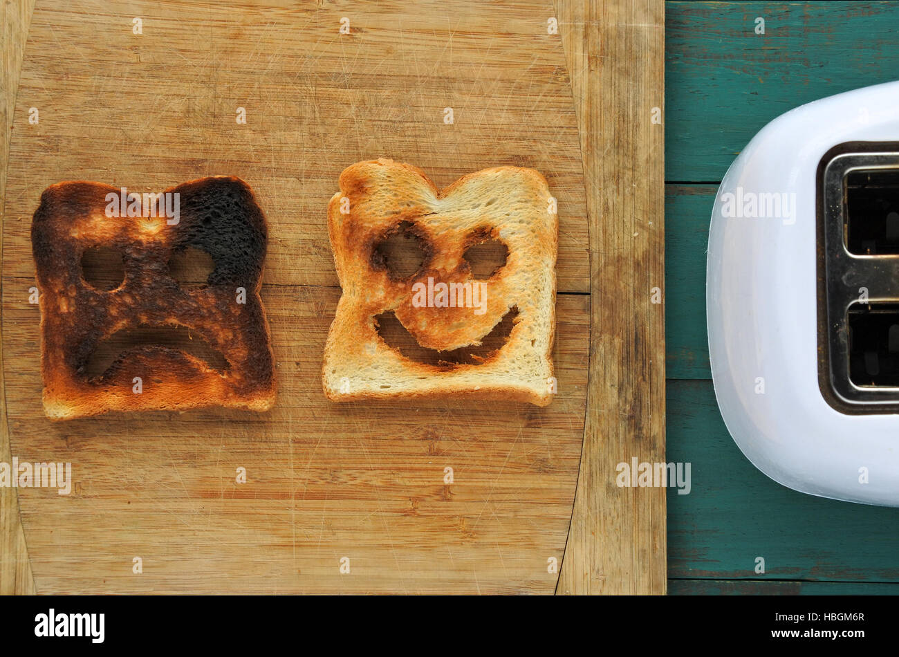 Flat lay view of two slices of toasted bread on a wooden board beside a toaster. One is burned and one is well done. - Stock Image