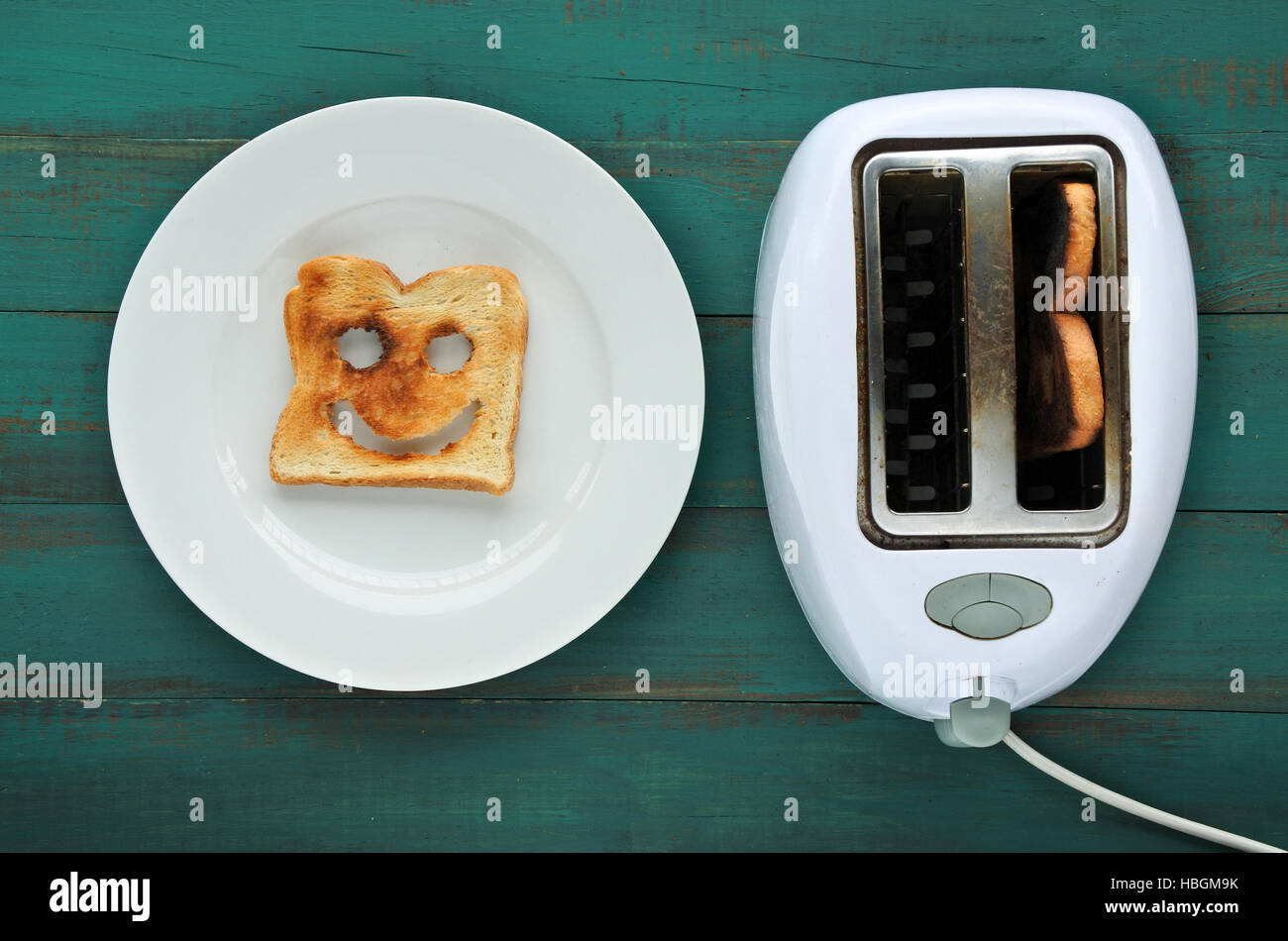 Flat lay view of one slices of  toast bread in a plate beside a toaster. Happiness  concept. copy space - Stock Image