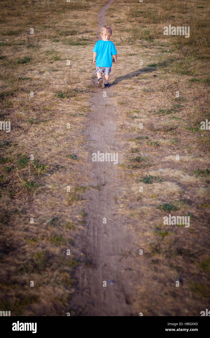 Little boy on a lonely walk Stock Photo