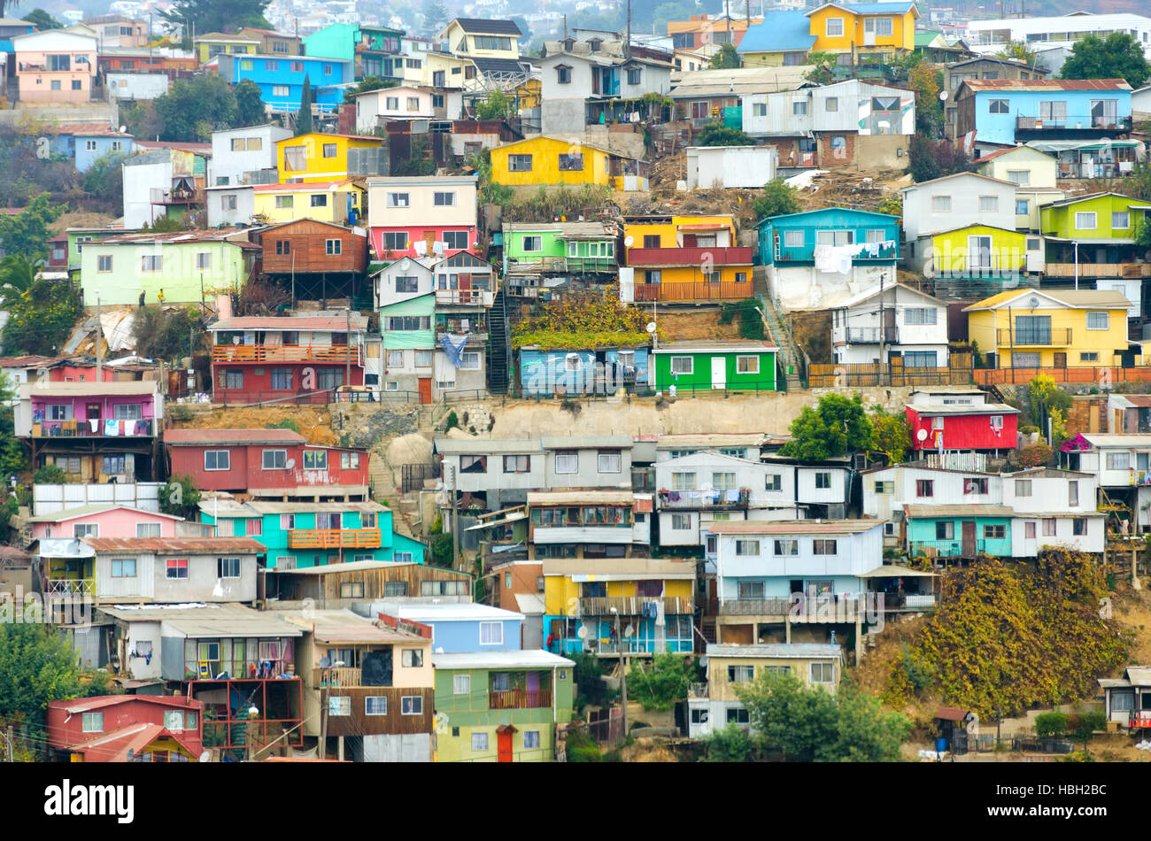 Brightly-colored houses tumble merrily down the sheer hills of Valparaiso, Chile - Stock Image