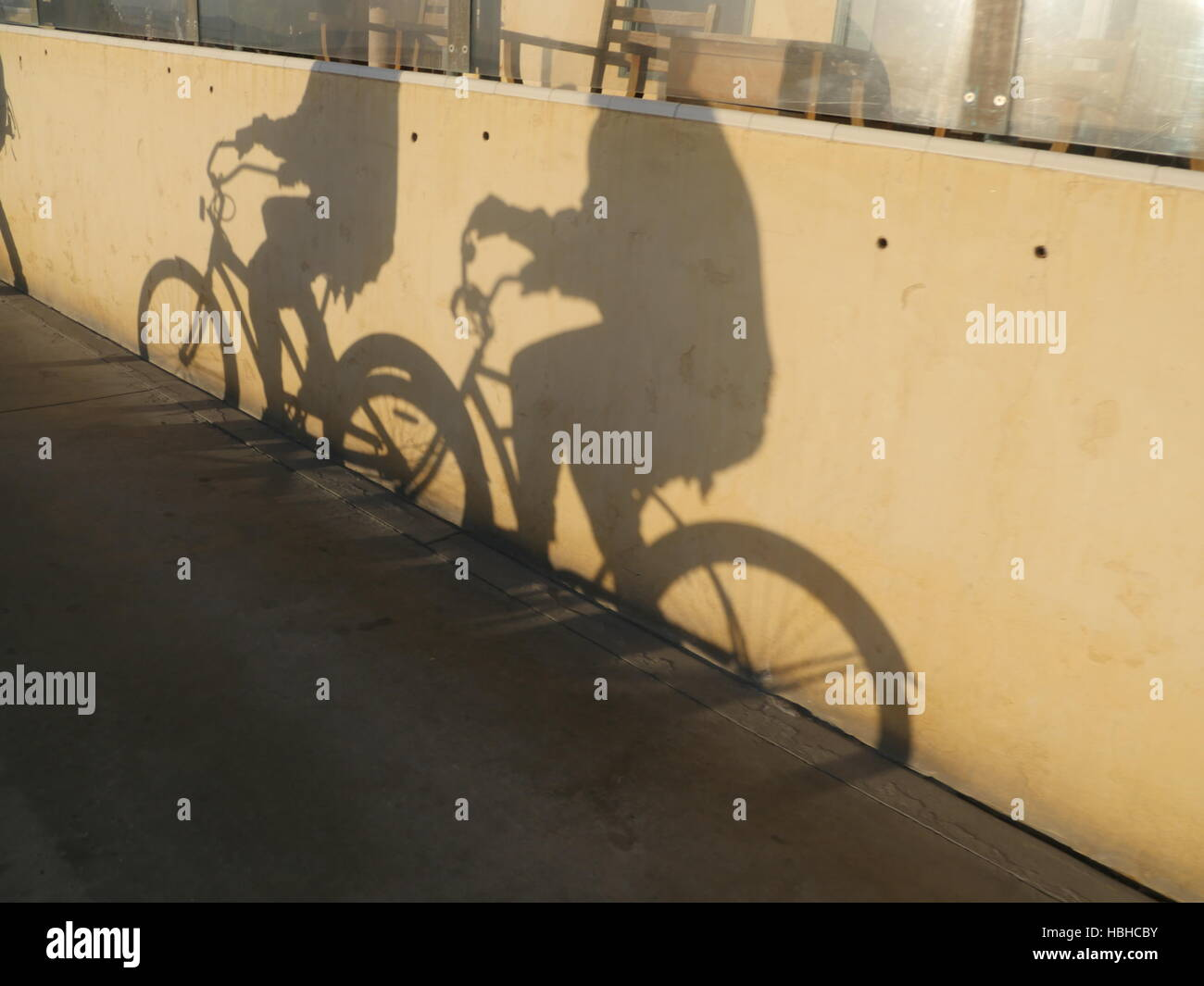 Two people riding bikes. Their shadows on wall Stock Photo ...