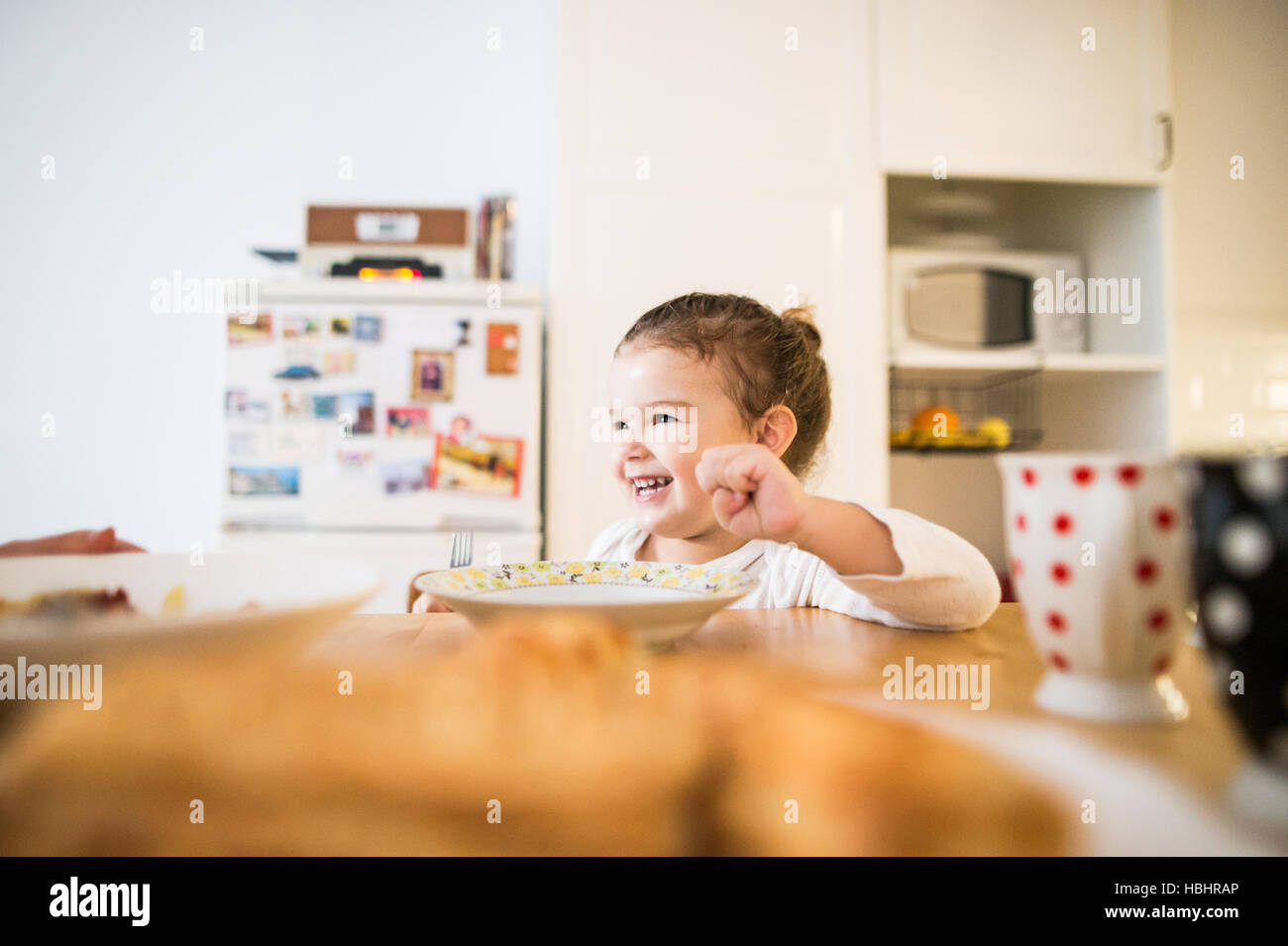 Little girl sitting at the table, eating breakfast - Stock Image