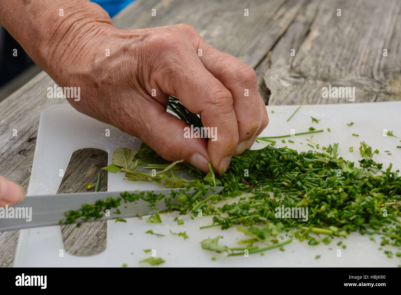 Cut chives on plate by hand with a knife Stock Photo