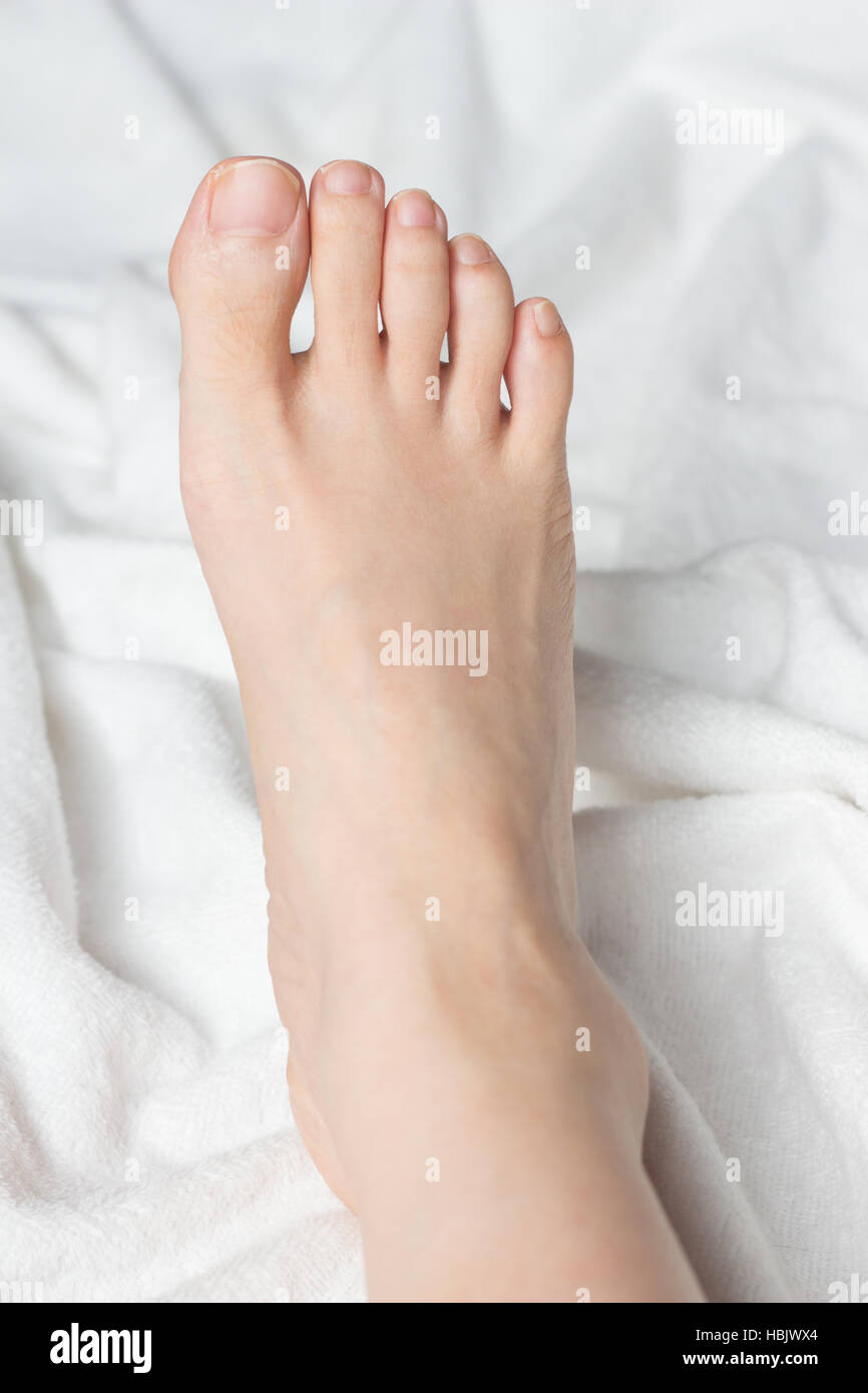Young woman's bare foot on white blanket - Stock Image