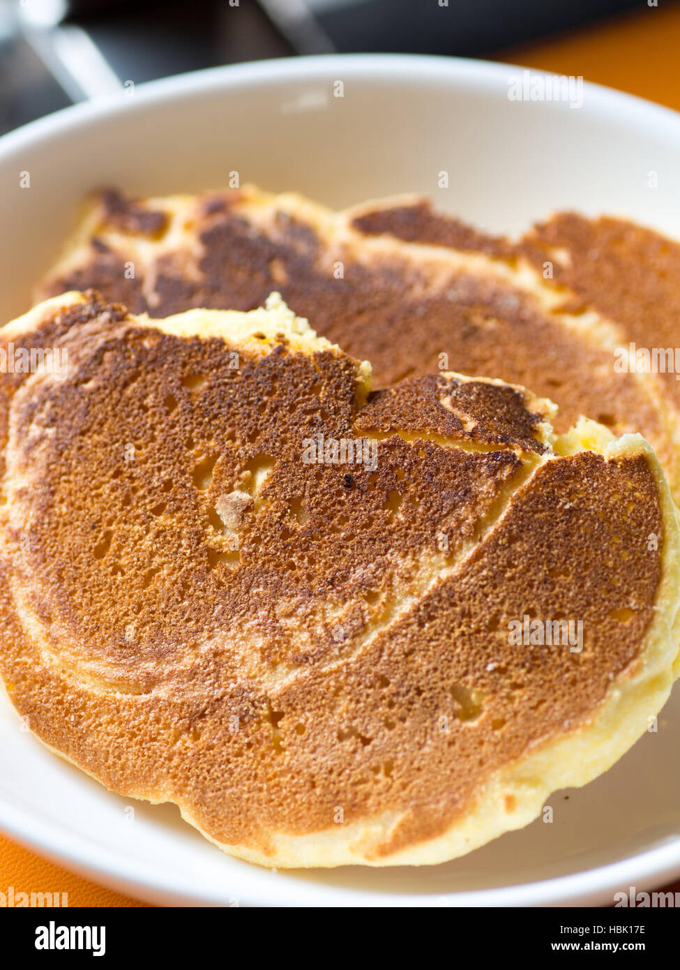 Simple and plane cornmeal pancakes on the white plate - Stock Image