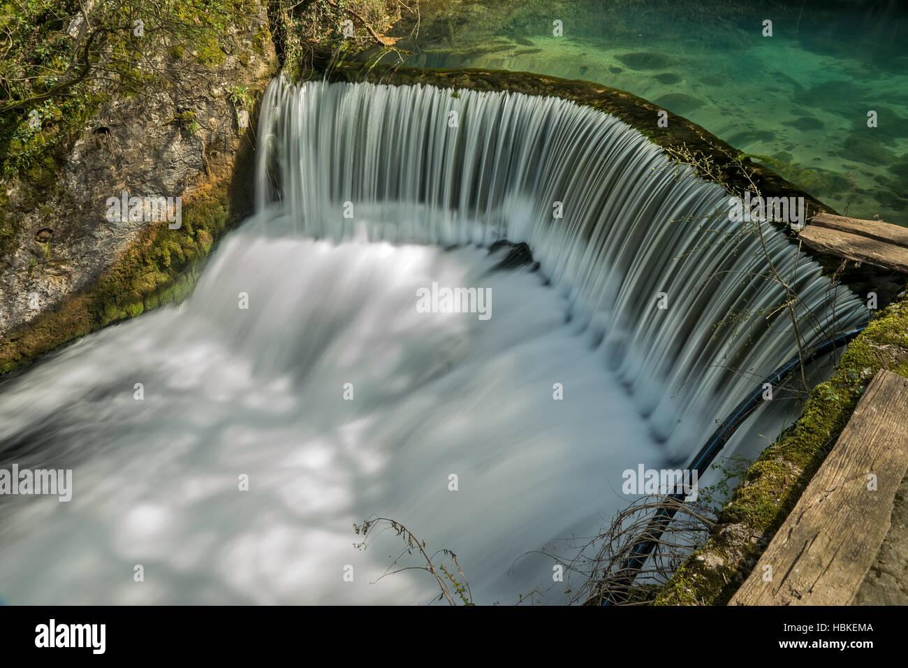 Semicircular dam with small lake that cause waterfall on river Rasina in Serbia - Stock Image