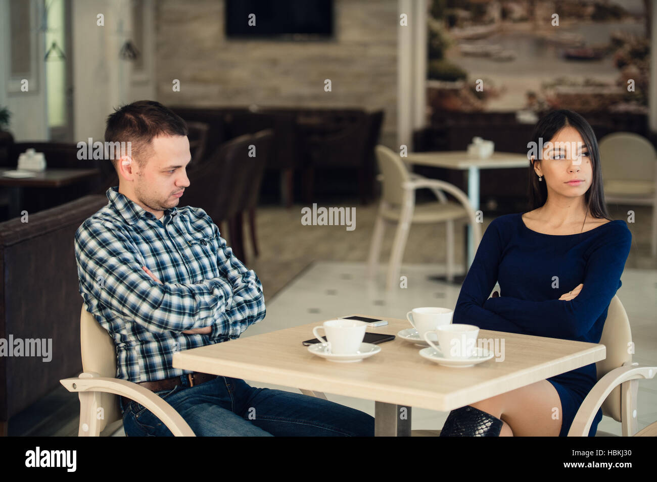 Young unhappy married couple having serious quarrel at cafe - Stock Image