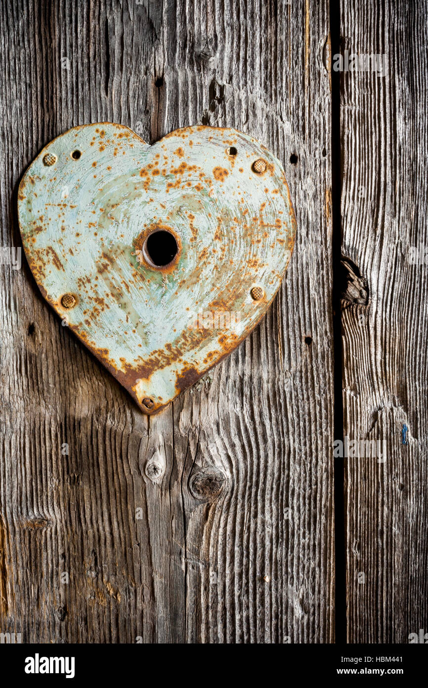 Rusty old trim on keyhole in shape of heart on old wooden door. Vertical shot. Stock Photo
