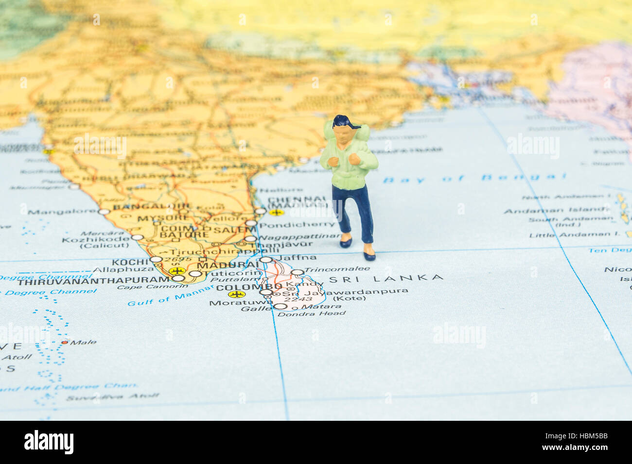 closeup of miniature figurine of young traveller standing on big map next to Sri lanka islands - Stock Image