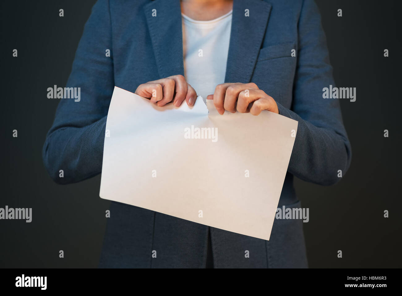 Unsatisfied and angry businesswoman tearing business legal agreement contract paper - Stock Image