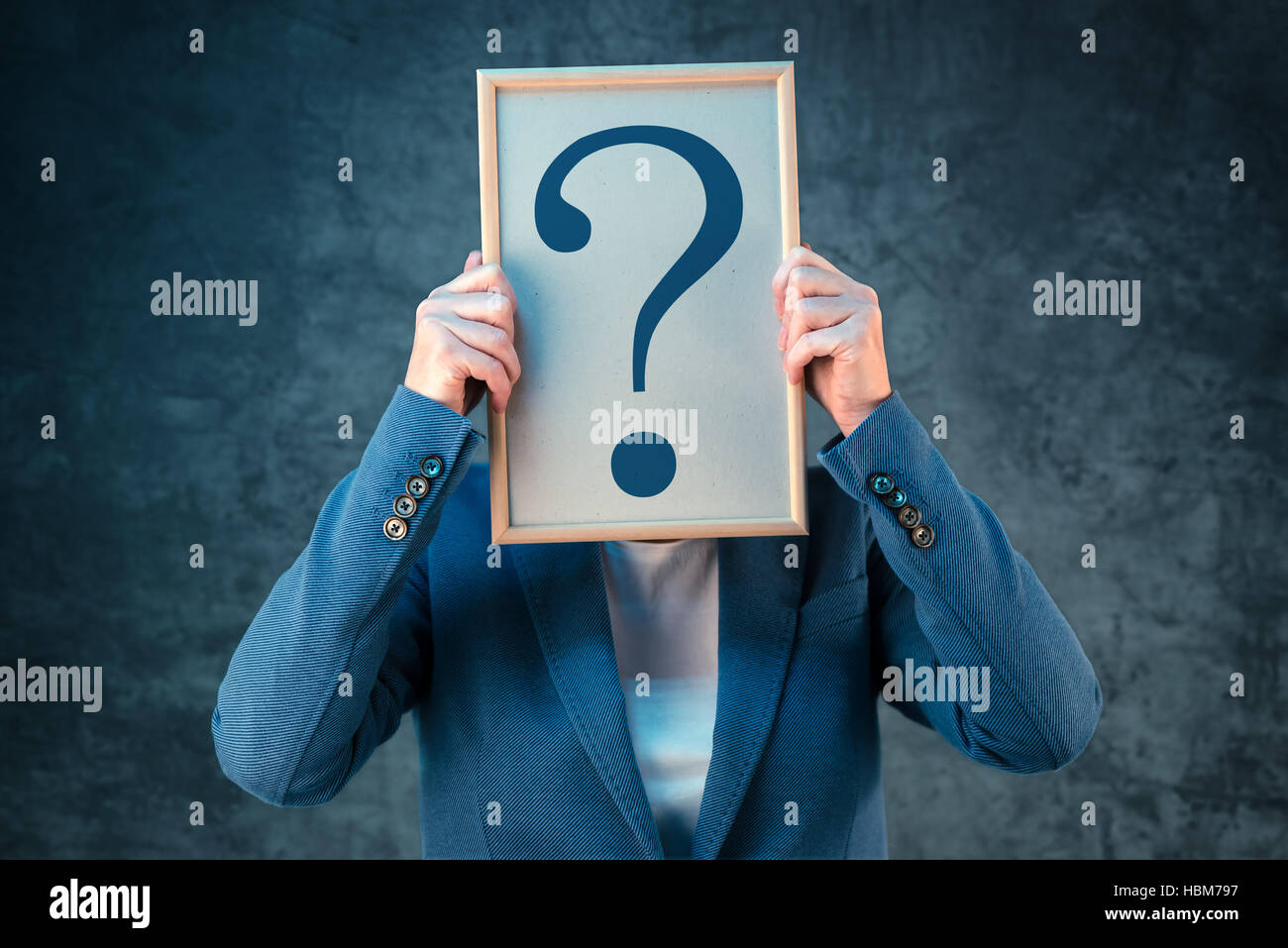 Businesswoman with question mark looking for answers, questioning and wondering about uncertain future in corporate - Stock Image