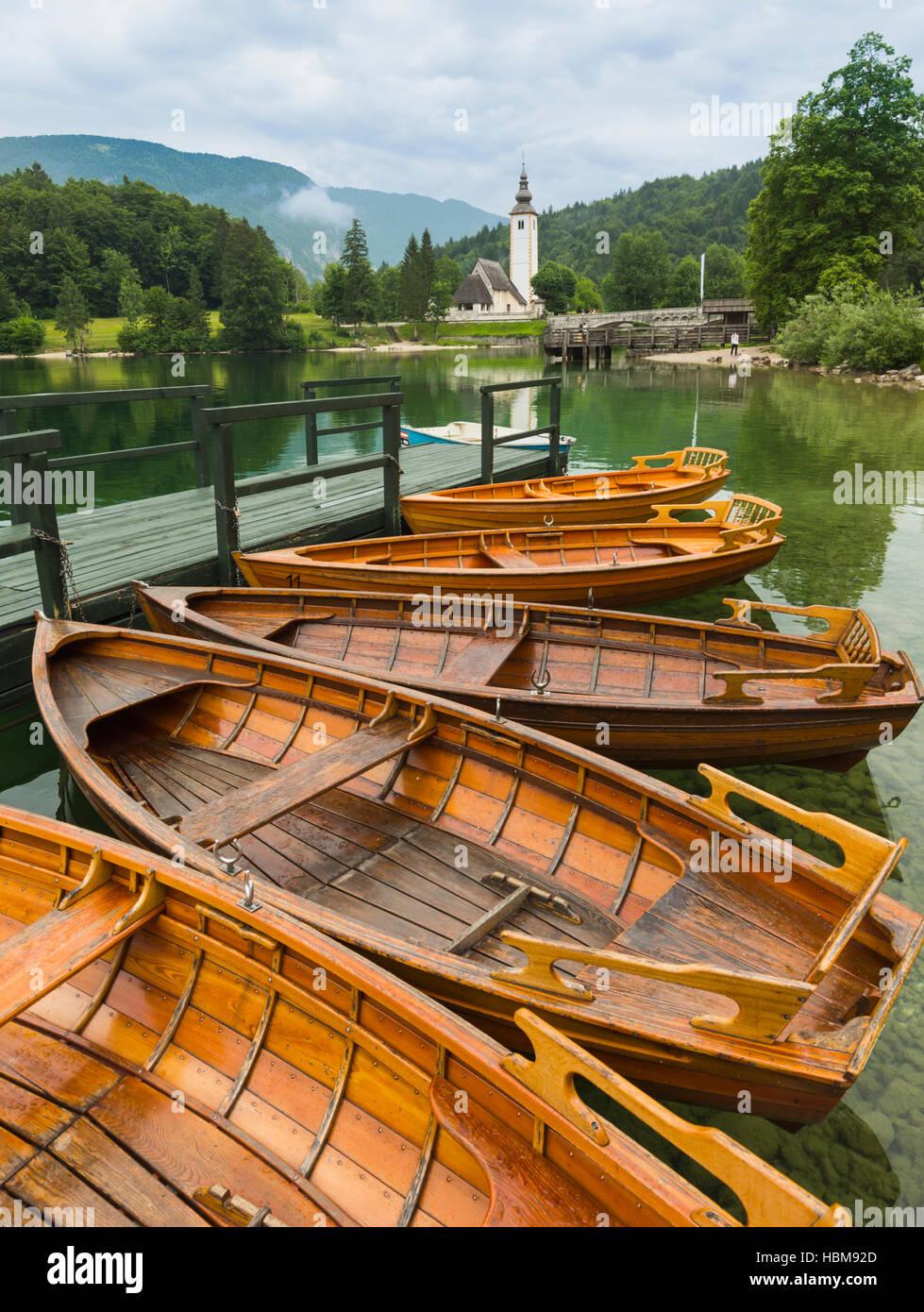 Lake Bohinj (Bohinjsko jezero), Triglav National Park, Upper Carniola, Slovenia. Rowing boats for rent. The church - Stock Image