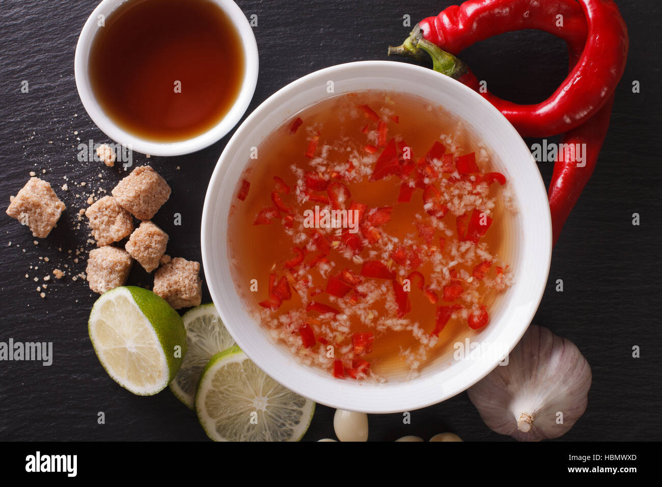 Vietnamese traditional Nuoc Cham sauce close up in a bowl and ingredients. horizontal view from above - Stock Image