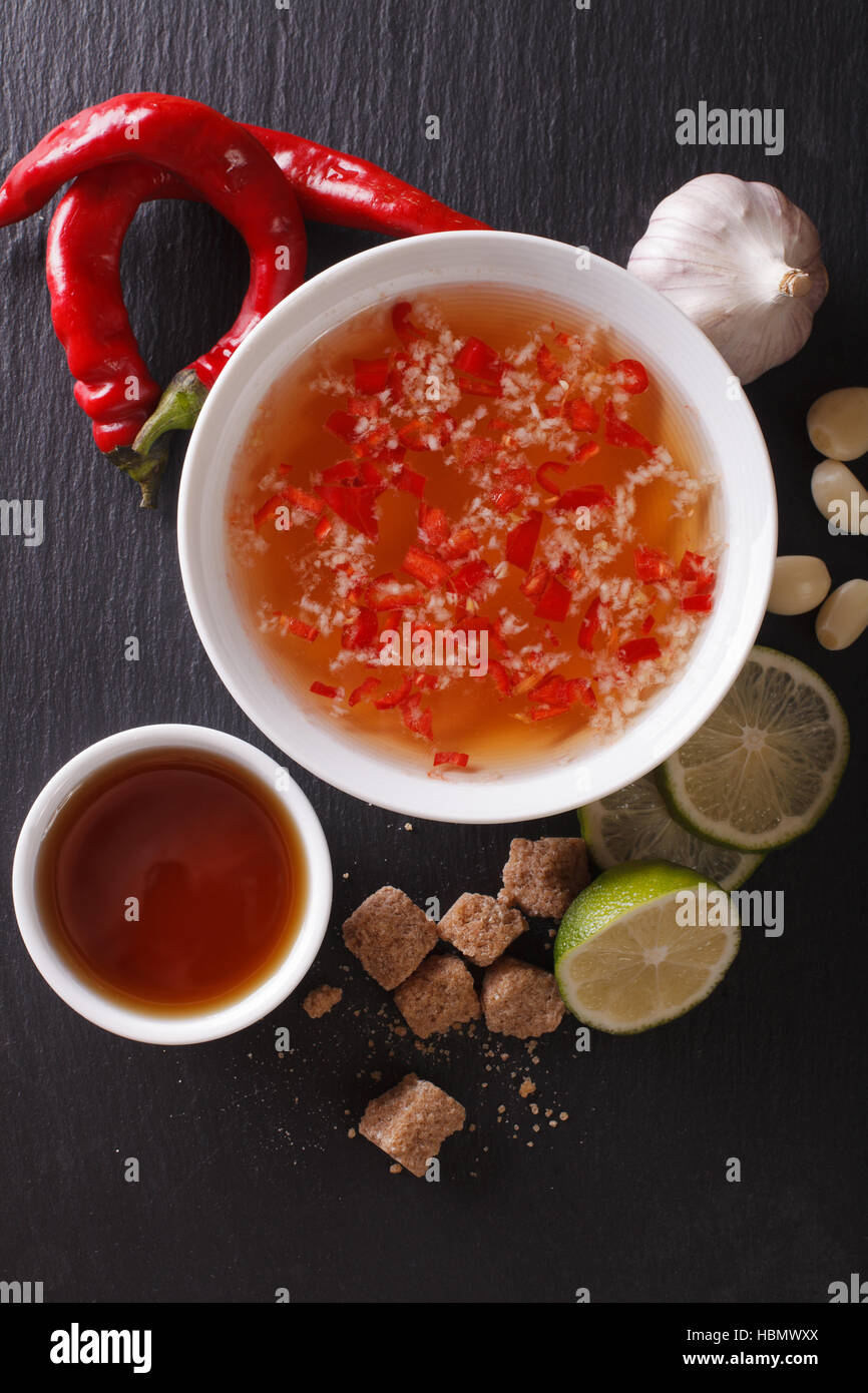 Vietnamese spicy sauce Nuoc Cham with the ingredients in a bowl close-up. vertical view from above - Stock Image