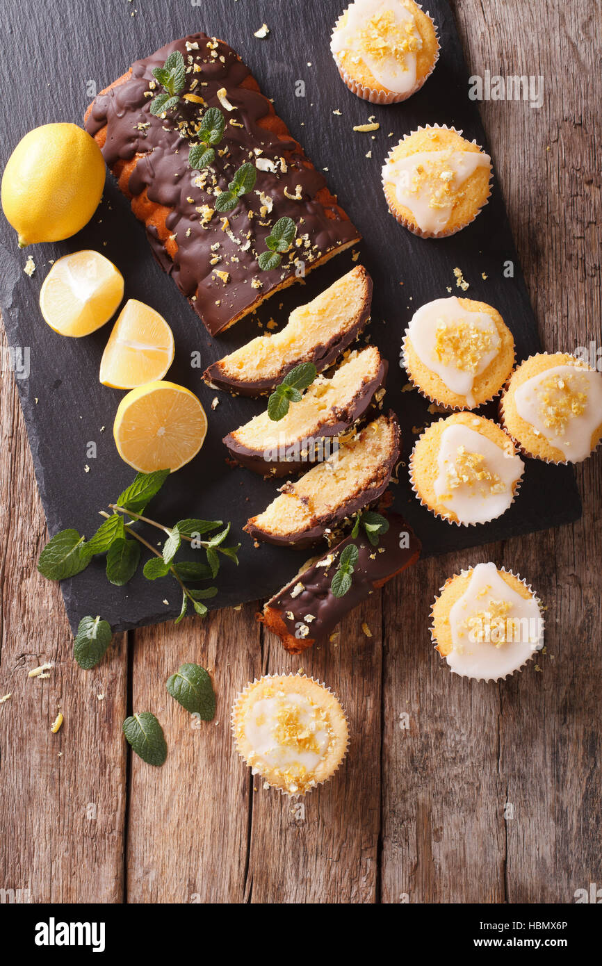 Sliced lemon cake with chocolate and lemon muffins with icing and zest close-up on the table. vertical view from - Stock Image