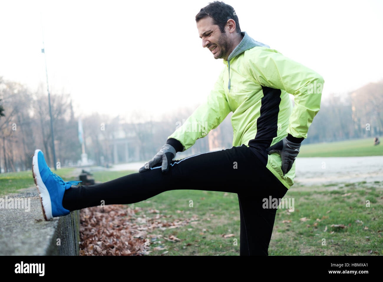 Man working out in the city park and stretching muscles - Stock Image
