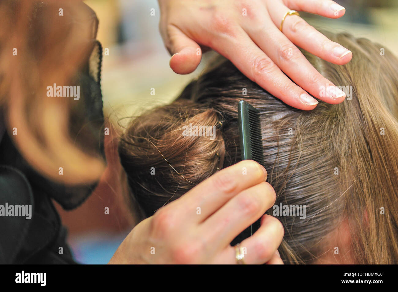 Hairdresser styling hair at the salon - Stock Image