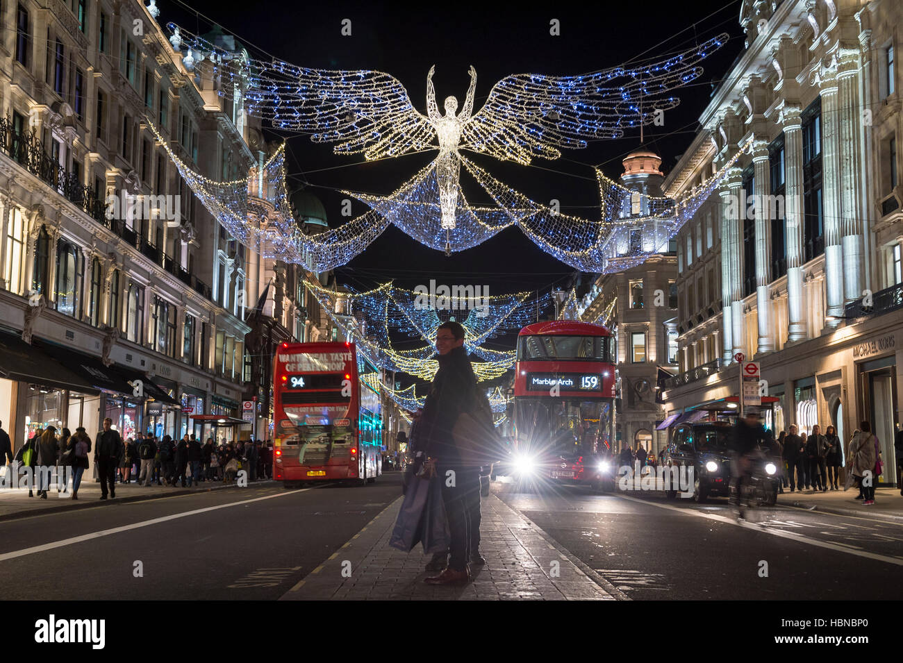 LONDON - DECEMBER 4, 2016: A pedestrian stops in the traffic median under twinkling Christmas angels lighting up - Stock Image
