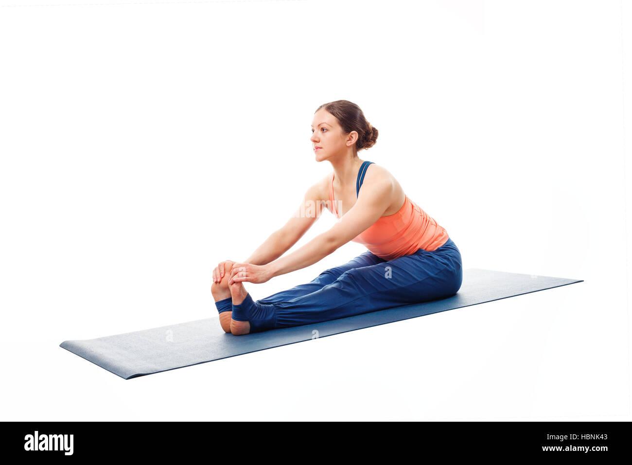 Woman doing Ashtanga Vinyasa Yoga asana Paschimottanasana - Stock Image