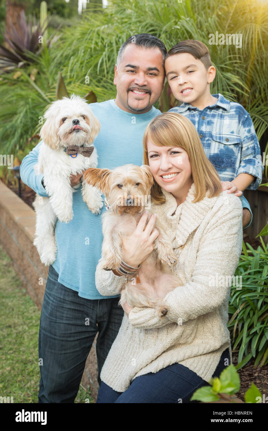 Happy Mixed Race Family with Dogs Portrait Outdoors. - Stock Image