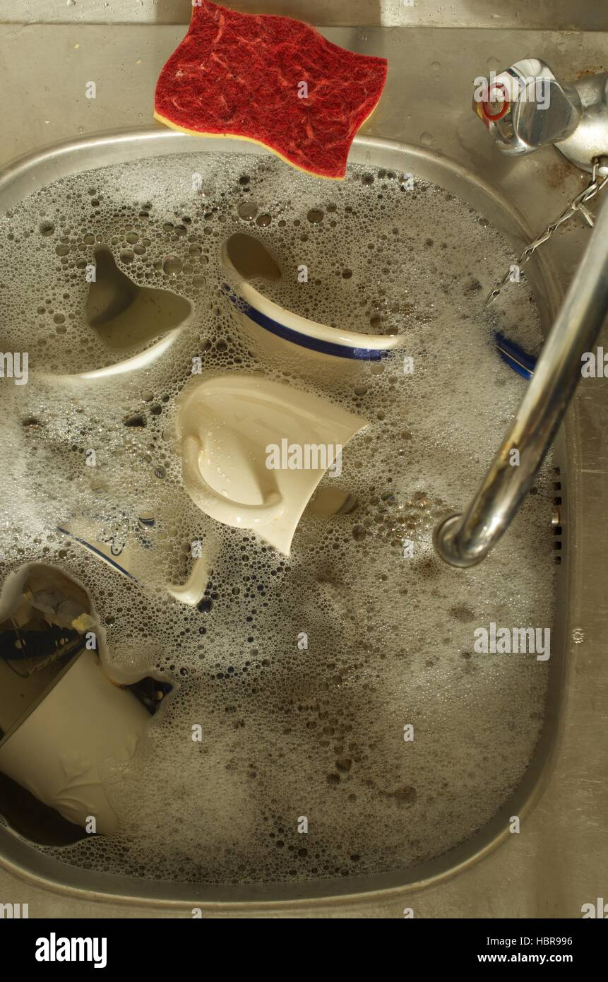 Washing up in a kitchen sink - Stock Image