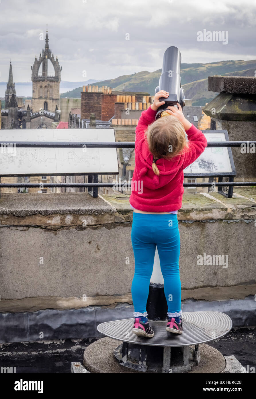 Little girl looking through the telescope - Stock Image