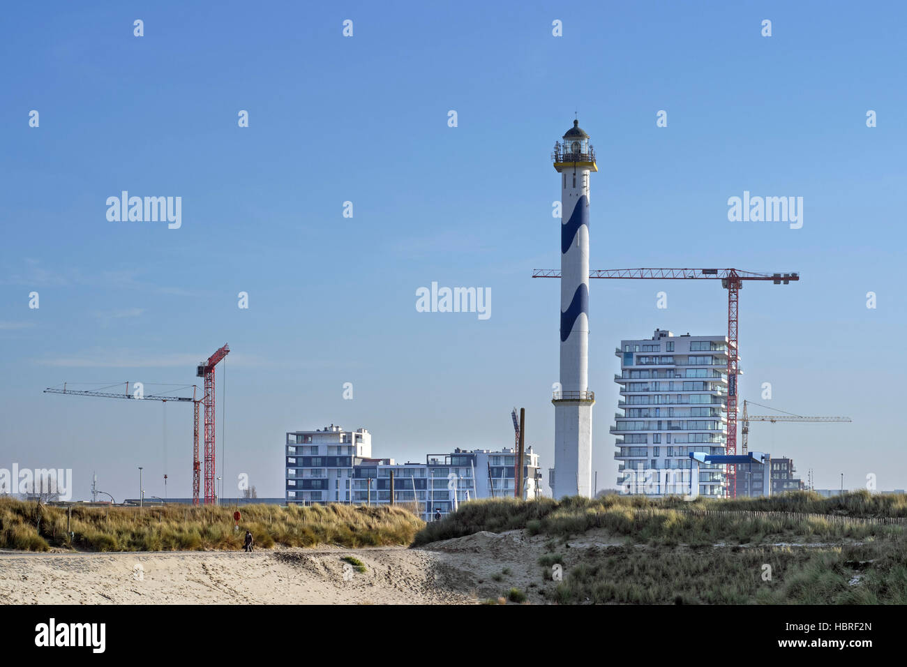 Lighthouse Lange Nelle and new flats being build for real estate project Oosteroever in the Ostend harbour along - Stock Image