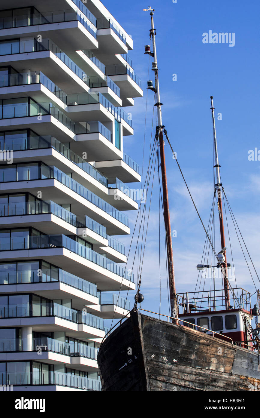 Old fishing boat and new flat being build for real estate project Oosteroever in the Ostend harbour along the Belgian - Stock Image
