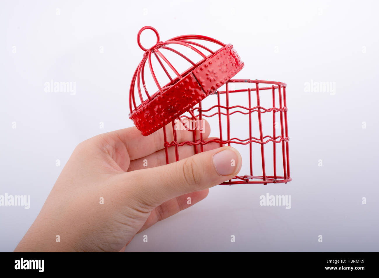 Little red color bird house with metal bars on a white background ...