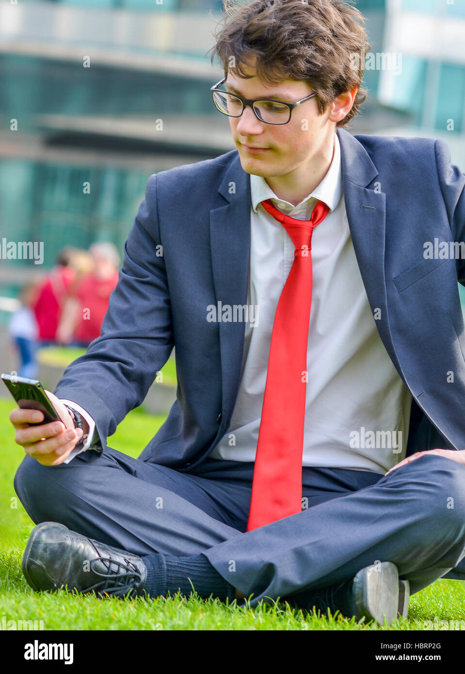 young businessman sitting on the grass Stock Photo