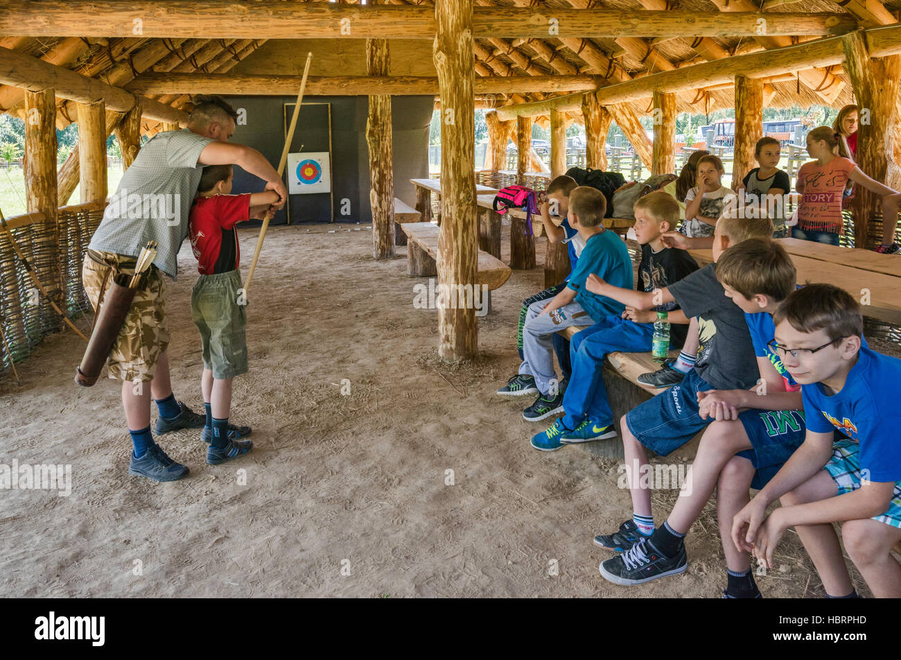 Young boy learning to shoot with a bow, Carpathian Troy Archaeological Open-Air Museum in Trzcinica near Jaslo, - Stock Image