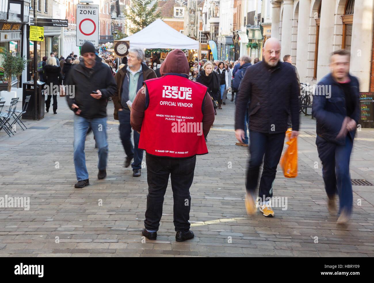 People walking past a Big Issue magazine vendor, Winchester, Hampshire, UK - Stock Image