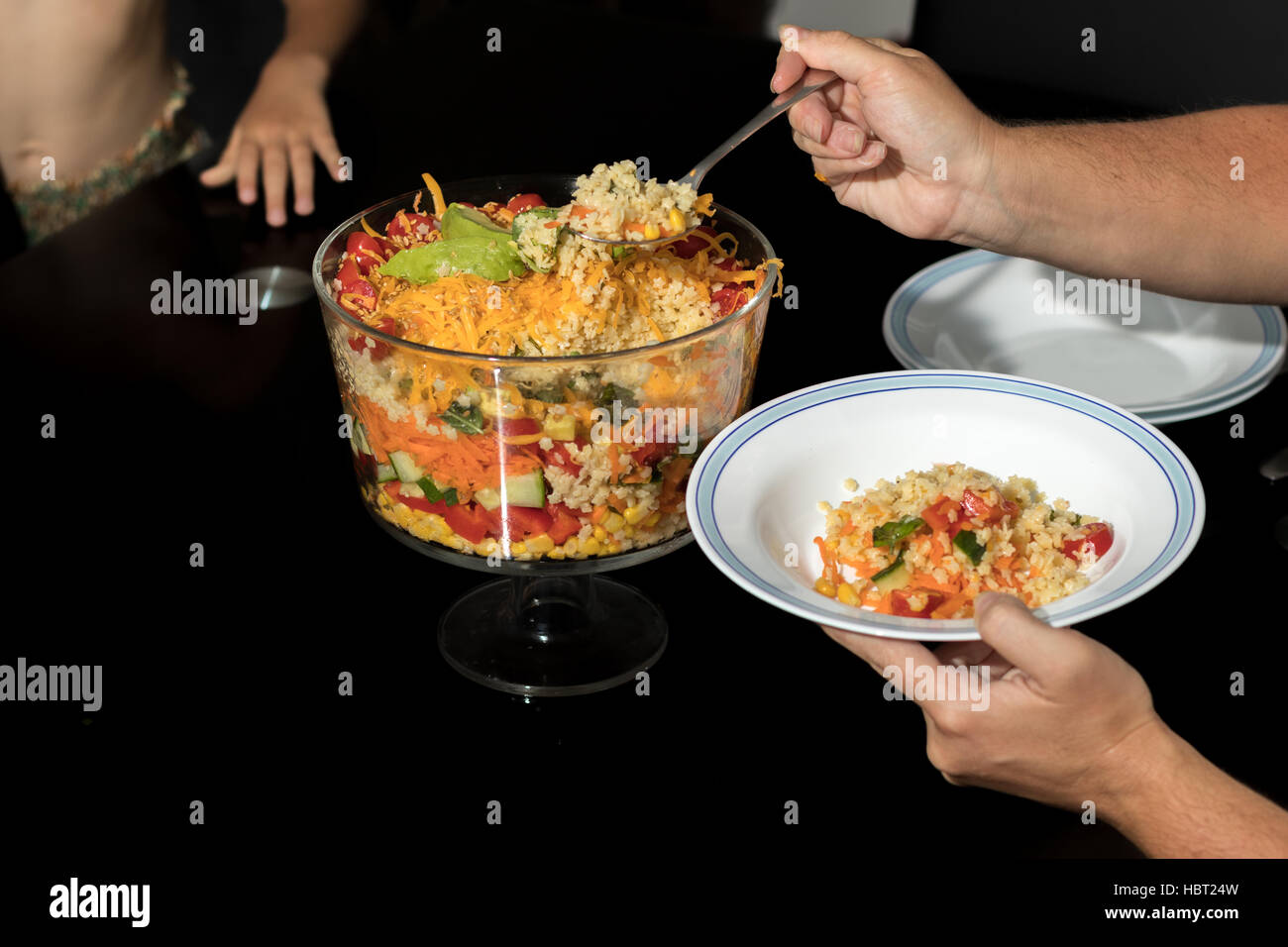 Mom serving plate of Multi Layered Salad - Stock Image