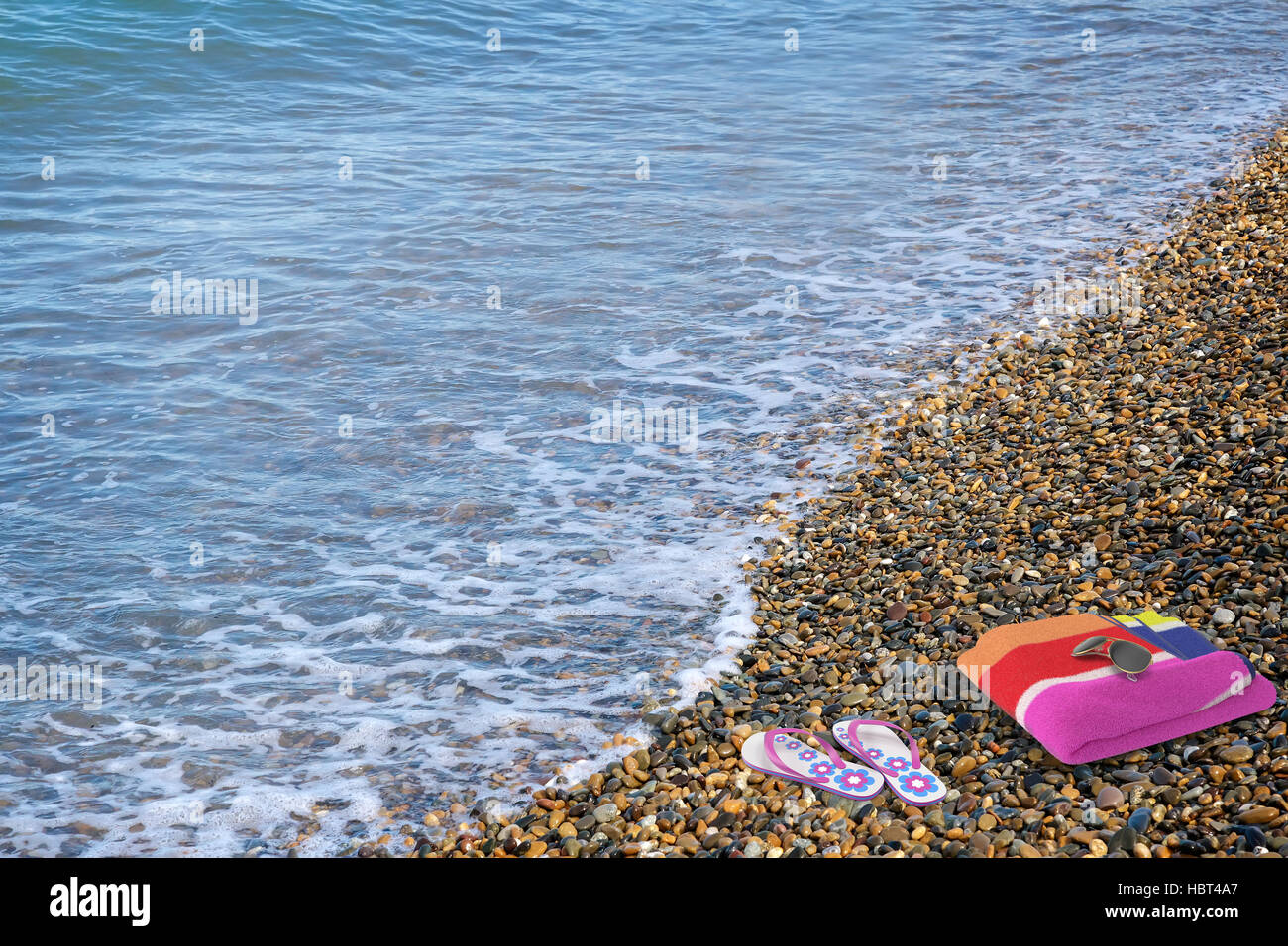 Beach shoes and a towel on the beach. - Stock Image