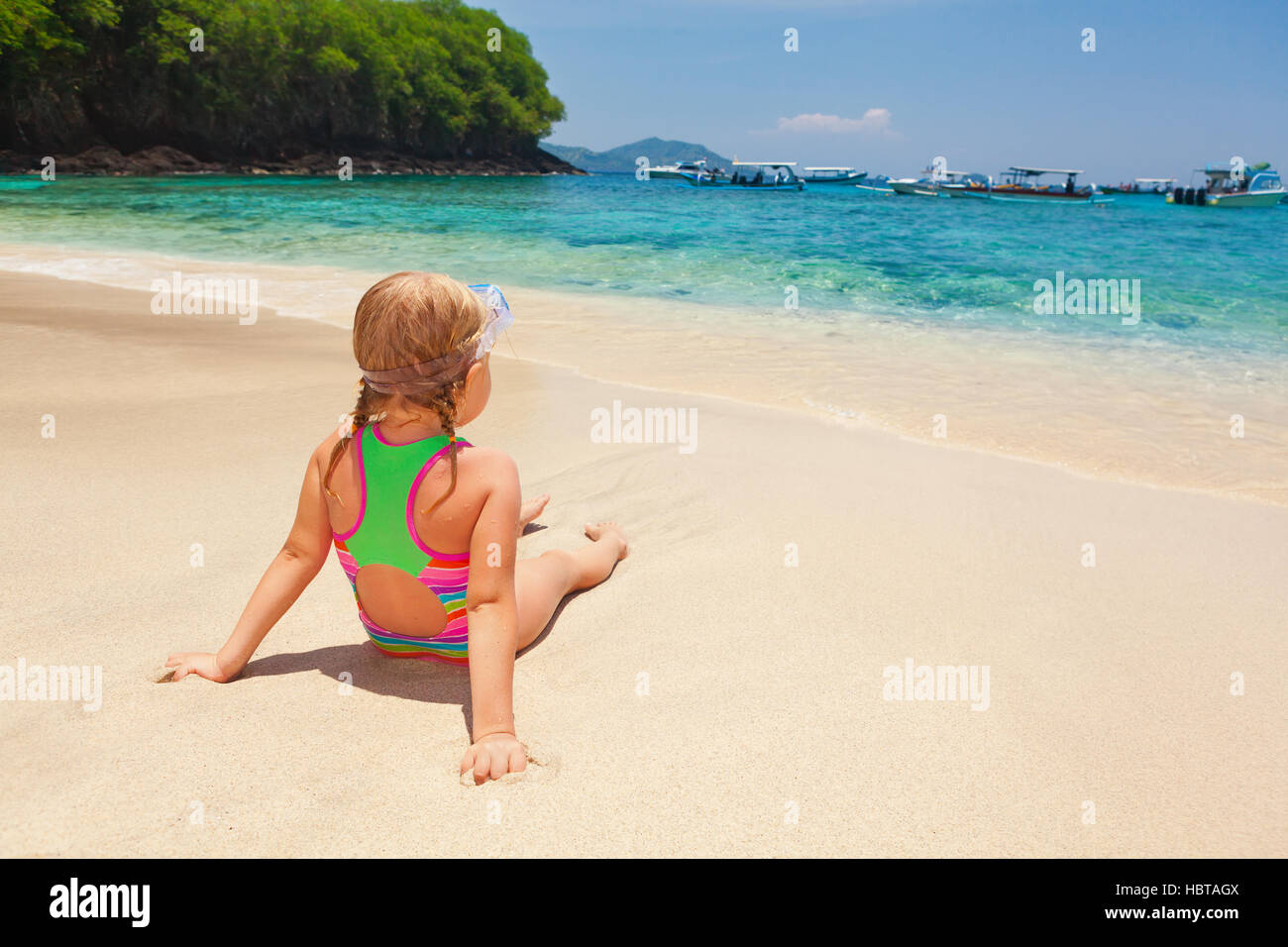 Beautiful little snorkeler relax on sunny white sand ocean beach. Happy baby have fun, look at surf in tropic blue - Stock Image
