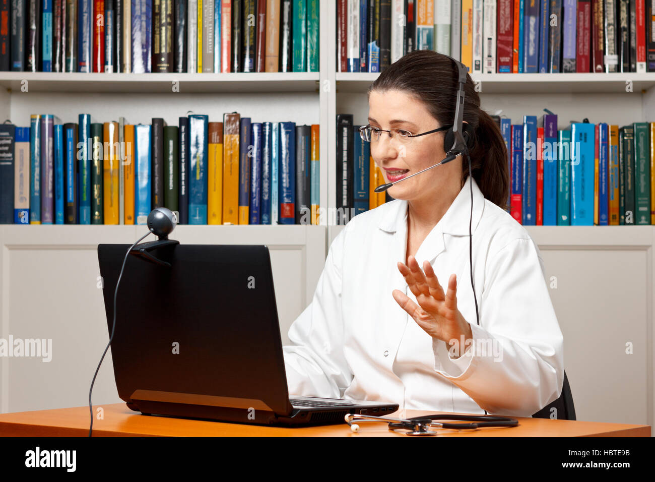 Doctor sitting with a headset or headphone at her desk in front of a computer with an attached camera and talking with a patient Stock Photo