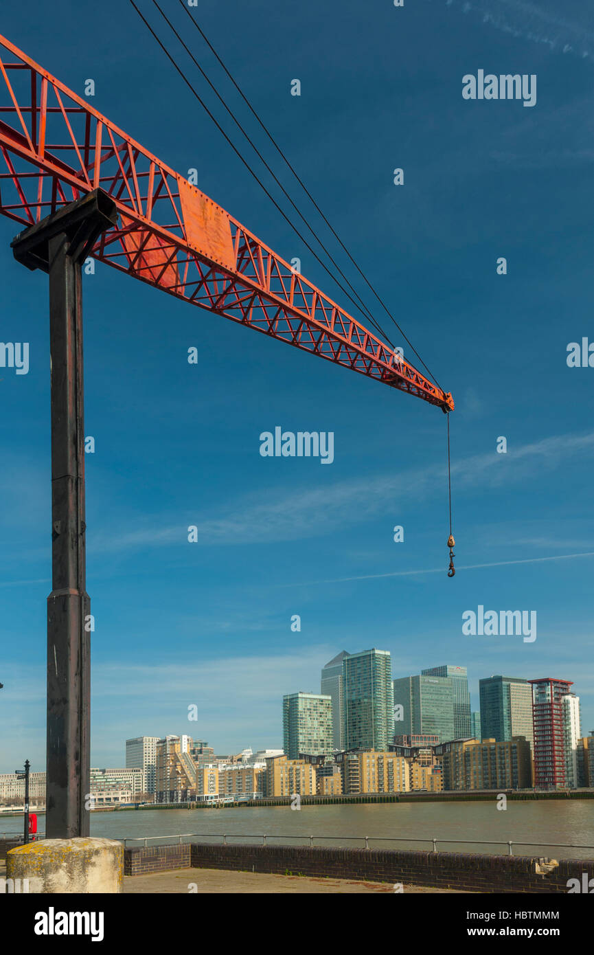 Old crane on the banks of the thames at Docklands Rotherhithe London. With Canary Wharf tower. - Stock Image