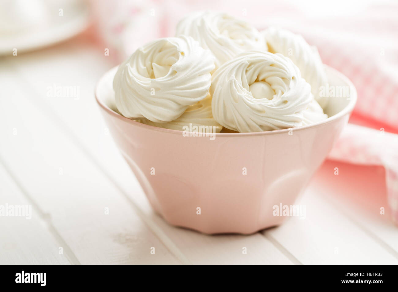Sweet white meringue in bowl. - Stock Image