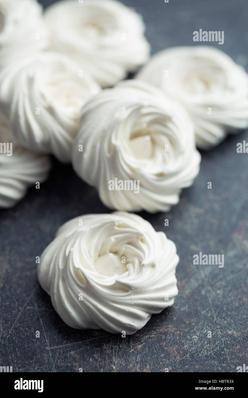 Sweet white meringue on black kitchen table. - Stock Image