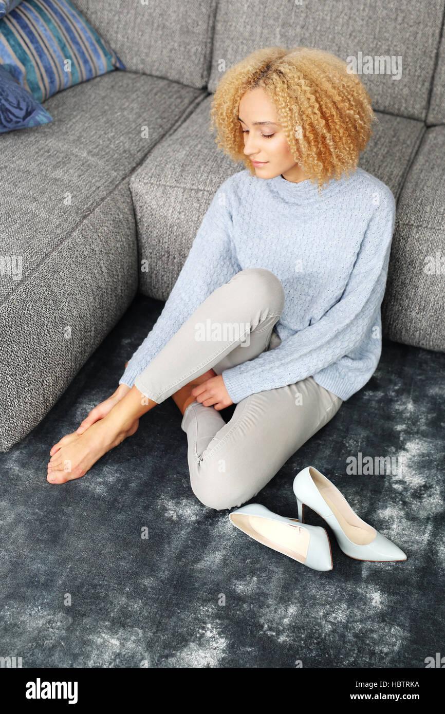Foot massage. Aching feet. Woman massaging tired, aching feet. - Stock Image