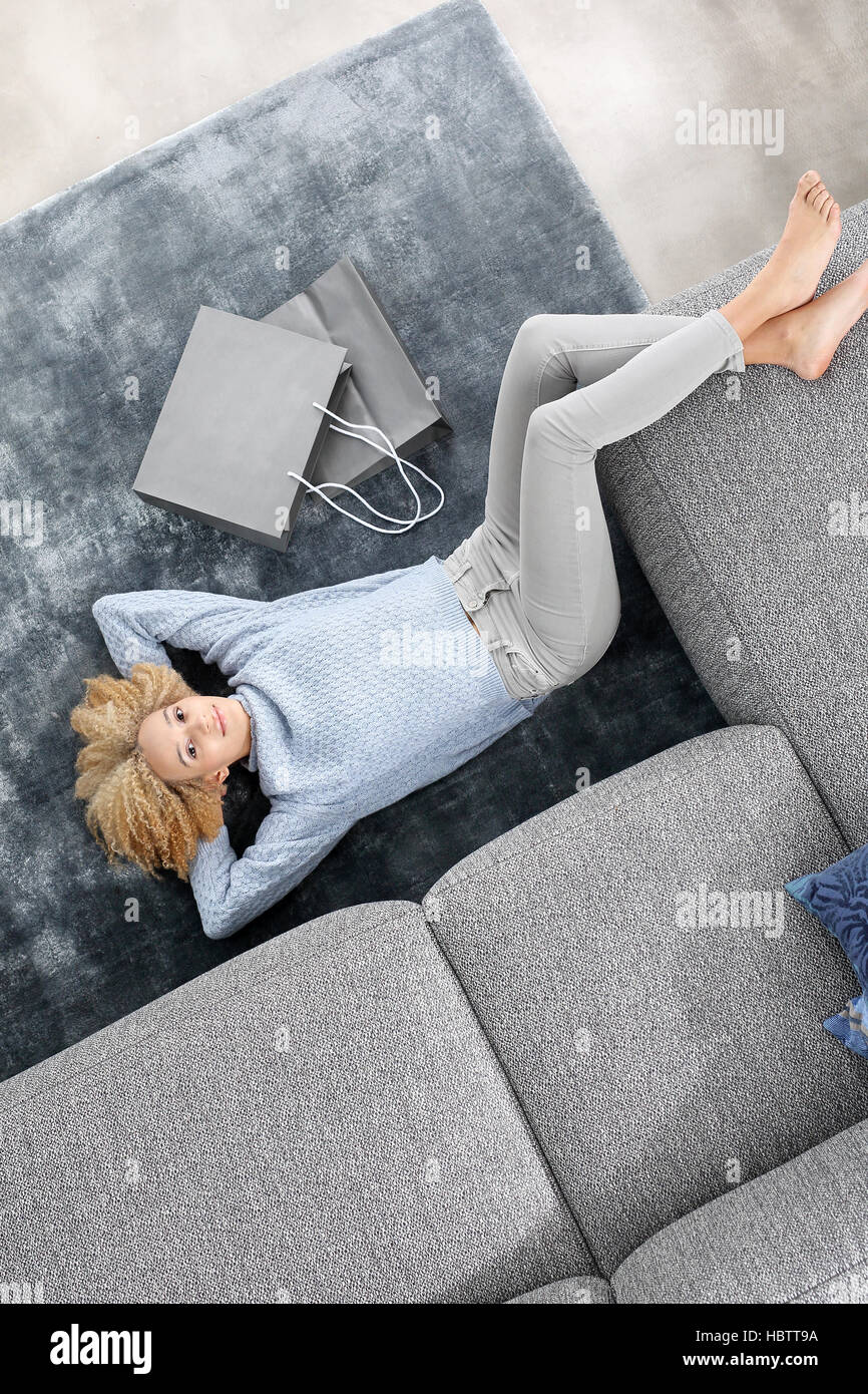 Woman lying on the carpet with her legs on the sofa. Aching feet. Relax in the comfort of your home. - Stock Image