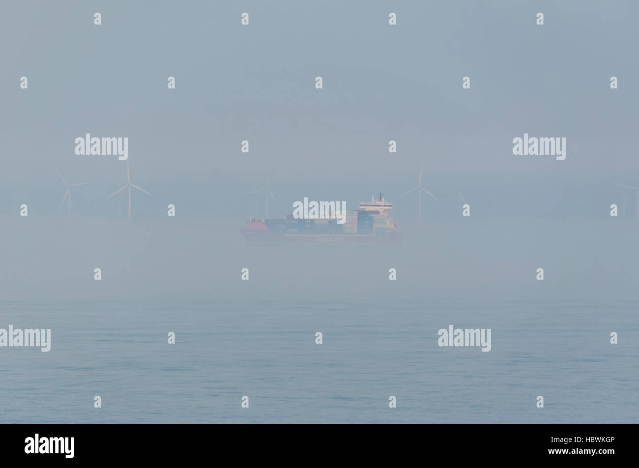 Container ship passing an offshore windpark during fog - Stock Image