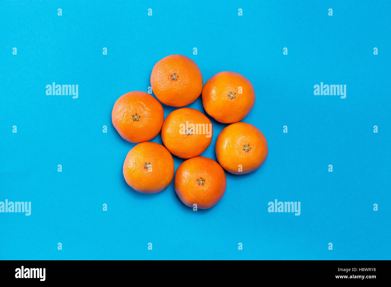 Six Colorful fresh orange mandarins laid out on blue table viewed from above with copy space. Concept sun on sky. - Stock Image