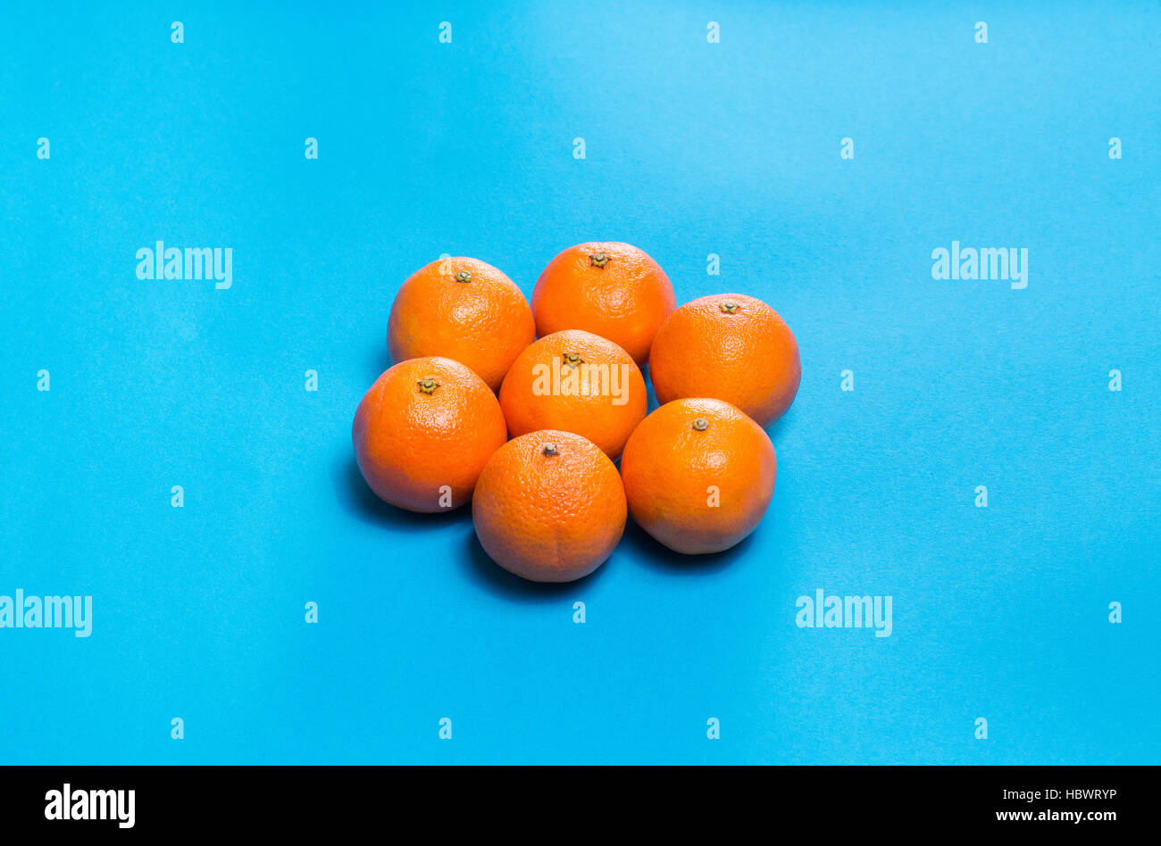 Sun symbol from Six Colorful fresh orange mandarins laid out on blue table viewed  above with copy space - Stock Image