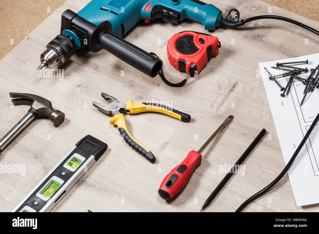 Set of construction tools to repair on a wooden surface: drill, hammer, pliers, self-tapping screws, roulette,  - Stock Image